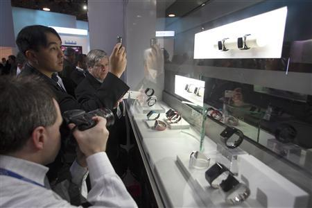Show attendees photograph a phone watch by LG Electronics during the 2009 International Consumer Electronics Show (CES) in Las Vegas, Nevada January 9, 2009. REUTERS/Steve Marcus