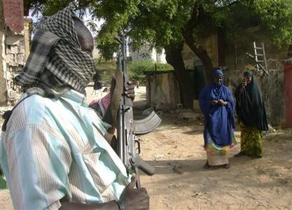 Somali women stand near an Islamist insurgent fighter at one of the bases vacated by Ethiopian troops in the capital Mogadishu January 13, 2009. REUTERS/Ismail Taxta