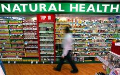 <p>A store worker walks past rows of herbal, vitamin and mineral pill products at a suburban pharmacy in Sydney April 29, 2003. REUTERS/David Gray</p>