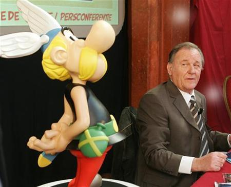 Albert Uderzo, the artist of all thirty-three Asterix adventures and the story writer of the last nine books, sits next to a model of Asterix at a news conference in Brussels September 22, 2005. REUTERS/Yves Herman