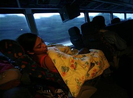 A woman sleeps on a Greyhound bus after a stop in Richmond, Virginia August 12, 2008. REUTERS/Shannon Stapleton