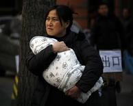 <p>A mother carries her baby wrapped in a blanket out of a hospital for children in Beijing January 16, 2009. REUTERS/David Gray</p>