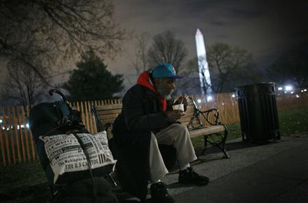 A homeless man sits on a bench with a cup of chili that he received from the Salvation Army's ''Gate Patrol'' in Washington, December 9, 2008. The Patrol runs every night providing food and clothing in the city for up to 200 homeless people and the working poor. Picture taken December 9, 2008. To match feature USA-ECONOMY/POVERTY REUTERS/Jim Young