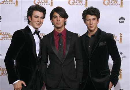 The Jonas Brothers (L-R), Kevin Jonas, Joe Jonas and Nick Jonas pose backstage after presenting at the 66th annual Golden Globe awards in Beverly Hills, January 11, 2009. REUTERS/Lucy Nicholson
