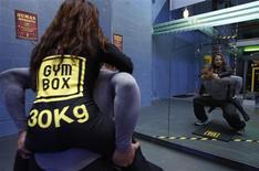 <p>Un instructor de ejercicios realiza sentadillas en el gimnasio Gymbox de Londres, 21 ene 2009. Un gimnasio británico está tratando de darle un toque personal a las monótonas rutinas de ejercicios, al reemplazar las tradicionales pesas metálicas por seres humanos. REUTERS/Stephen Hird</p>