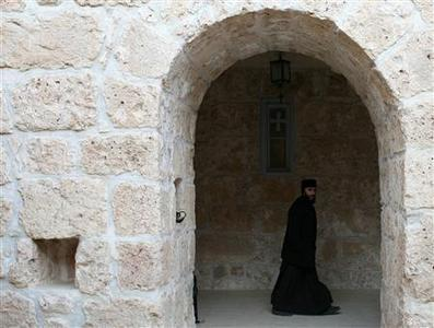 A Syriac Christian monk walks to attend a service at the ancient monastery of Mor Gabriel, 15 km (9 miles) from the town of Midyat, in Mardin province of southeast Turkey January 13, 2009. Tucked amid rugged hills where mosques and minarets are silhouetted in the distance, the fifth century Mor Gabriel monastery stands out as a relic of another era when hundreds of thousands of Syriac Christians lived and worshipped in Turkey. But a land dispute between Mor Gabriel and neighbouring villages is threatening the monastery's future. Picture taken January 13, 2009. To match feature RELIGION-TURKEY/CHRISTIANS REUTERS/Umit Bektas