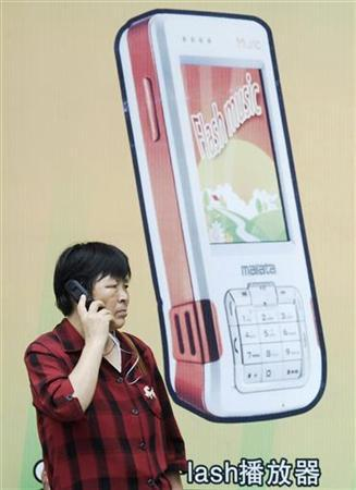 A woman speaks on a mobile phone in front of a billboard in Xiangfan, Hubei province June 21, 2008. REUTERS/Stringer
