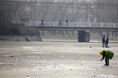 <p>A fisherman makes a hole in a frozen canal using an ice-pick, in central Beijing January 23, 2009. REUTERS/David Gray</p>