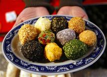 <p>A woman poses with a plate of rice cake balls at the Dihua Chinese Lunar New Year street market in Taipei January 23, 2009. REUTERS/Nicky Loh</p>