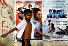 "<p>A boy walks past publicity posters of Golden Globe award-winning film ""Slumdog Millionaire"" in Mumbai, January 22, 2009. REUTERS/Arko Datta</p>"