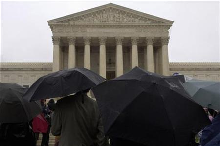 Tourists and protesters stand in the rain outside the Supreme Court in Washington November 8, 2006. REUTERS/Jonathan Ernst