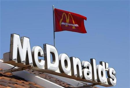 A flag blows in the wind above a McDonald's restaurant in Encinitas, California July 21, 2008. REUTERS/Mike Blake