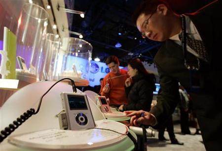 An attendee at the 2005 International Consumer Electronics Show (CES) looks over some mini video/music players from LG Electronics in Las Vegas, January 6, 2005. REUTERS/Mike Blake