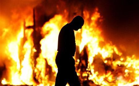A man walks past a burning vehicle in a Loyalist area in North Belfast September 12, 2005. REUTERS/Jeff J Mitchell