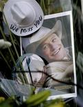 """<p>A photograph of Heath Ledger from the movie """"Brokeback Mountain"""" rests among flowers at a makeshift memorial in front of the building where the actor died in New York January 23, 2008. REUTERS/Nicholas Roberts</p>"""