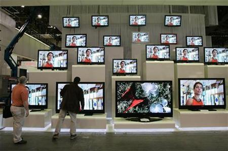 Exhibitors look over Samsung televisions in the Las Vegas Convention Center during set up for 2007 International CES (Consumer Electronics Show) in Las Vegas, Nevada in this file photo from January 6, 2007. REUTERS/Steve Marcus