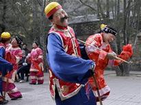 <p>Esibizione in costumi tradizionali in Cina,all'insegna dell'umorismo. REUTERS/David Gray</p>