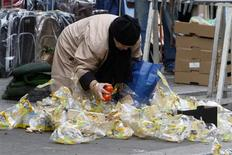 <p>A woman picks up discarded fruits and vegetables after a market in Paris February 4, 2009. REUTERS/Jacky Naegelen</p>