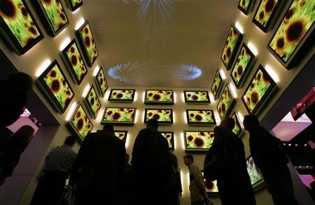 Attendees look up at a display of Panasonic plasma televisions at the 2005 International Consumer Electronics Show (CES) in Las Vegas, January 6, 2005. REUTERS/Mike Blake