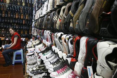 A shopkeeper, selling fake foreign brand shoes, waits for customers in Beijing May 8, 2008. REUTERS/Claro Cortes IV