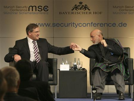 Afghan President Hamid Karzai (R) and German Defence Minister Franz Josef Jung shake hands during the 45th Munich Security Conference February 8, 2009. REUTERS/Sebastian Zwez/Pool (GERMANY)