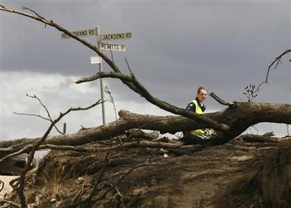 An Australian Federal policeman stands guard near the town of Kinglake, 46km (29 miles) north of Melbourne, February 10, 2009. Weary firefighters and rescuers pulled the remains of dozens of people from charred buildings Monday as the toll from Australia's deadliest bushfires rose to 171, police said. REUTERS/Daniel Munoz