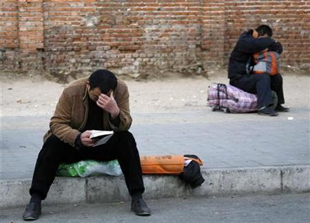 A migrant worker reads a book as another sleeps as they wait for potential employers to arrive at an unofficial labor market located near a bus station in central Beijing, February 11, 2009. REUTERS/David Gray