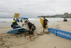 "<p>Two surfers walk as lifeguards set up ""dangerous current"" signs at the iconic Bondi beach in Sydney, February 13, 2009. REUTERS/Daniel Munoz</p>"