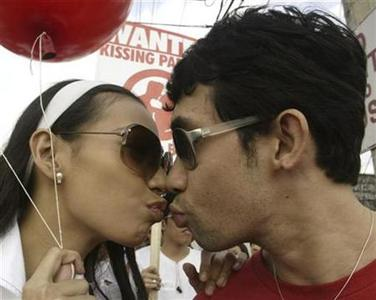 A Filipino couple kiss during a rally before marching towards the Hungarian embassy in Makati's financial district of Manila January 24, 2007, as a sign of their determination to regain the 'Kiss festival' record. REUTERS/Joseph Agcaoili