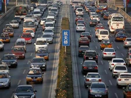 Cars travel closely behind each other along a main road in central Beijing November 19, 2008. REUTERS/David Gray