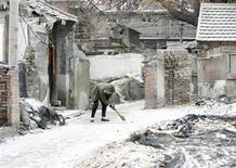 <p>A woman clears snow in front of her house in Beijing February 17, 2009. REUTERS/Christina Hu</p>