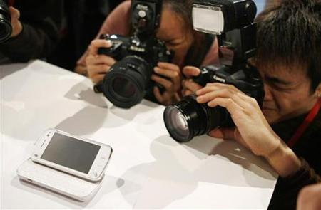 Journalists photograph a new 'Nokia N97' phone during the 'Nokia World 08' congress in Barcelona December 2, 2008. REUTERS/Albert Gea