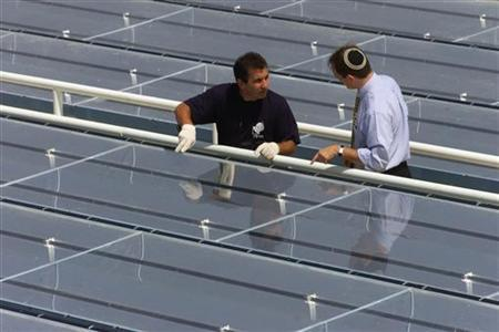 An Israeli engineer (L) explains an above-ground solar panel to a visitor at Israel's Solel Solar Systems Centre in Bet Shemesh September 20, 2000. REUTERS/Natalie Behring