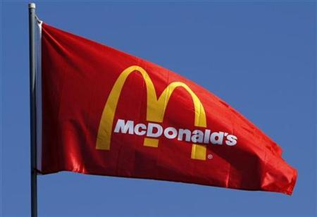 A flag blows in the wind above a McDonald's restaurant in Encinitas, California July 21, 2008. McDonald's, the world's biggest restaurant chain, reports second-quarter earnings later this week. Investors will be looking for how the company is controlling rising commodity prices. REUTERS/Mike Blake