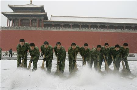 People's Liberation Army (PLA) soldiers sweep snow in front of the Forbidden City during a snowfall in Beijing February 18, 2009. REUTERS/China Daily