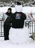 <p>A woman stands next to a snowman on Parliament Hill as she waits for U.S. President Barack Obama in Ottawa February 19, 2009. Obama is on his first foreign trip since taking office. REUTERS/Christinne Muschi</p>
