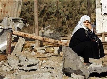 A Palestinian woman sits outside her house, destroyed after an Israeli air strike, near the border between Egypt and the southern Gaza Strip, February 7, 2009. REUTERS/Ibraheem Abu Mustafa