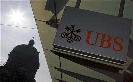 A UBS logo is pictured on a UBS bank building in front of the silhouetted Swiss federal parliament building in Bern February 19, 2009. REUTERS/Pascal Lauener