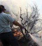 <p>A fireman fights to stop a forest fire tin southwest Cyprus June 18, 2008. REUTERS/Christos Theodoridis</p>