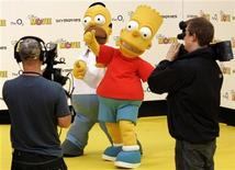 <p>Homer and Bart Simpson characters of the television programme The Simpsons pose for film crews at the UK premiere of The Simpsons Movie at the O2, formally known as the Millennium Dome in London July 25, 2007. REUTERS/Luke MacGregor</p>