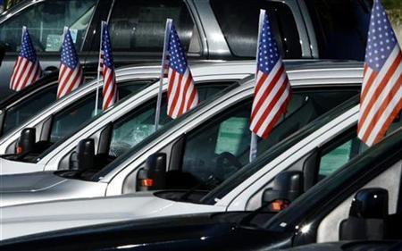Trucks displaying American flags are lined-up for sale at a local Ford auto dealership in Encinitas, California February 3, 2009. REUTERS/Mike Blake