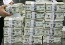<p>Сотрудник банка пересчитывает долларовые купюры в Сеуле 26 февраля 2009 года. Международные организации пообещали выделить до $4,481 миллиардов на поддержку палестинской экономики и восстановление Сектора Газа после авиаударов и наземной операции израильской армии. REUTERS/Lee Jae-Won</p>
