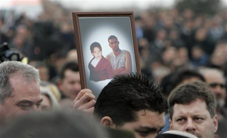 A mourner holds up a picture of Robert Csorba, 27, and his son Robert Jr., 5, during their funeral in Tatarszentgyorgy, 65 km (40 miles) southeast of Budapest March 3, 2009. REUTERS/Karoly Arvai
