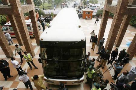 Members of the media gather around a bus, which was carrying the Lankan cricket team, parked outside the Gaddafi stadium in Lahore March 3, 2009. A dozen gunmen attacked Sri Lanka's cricket team on Tuesday with rifles, grenades and rockets, wounding six players and a British coach and killing at least eight Pakistanis in Lahore. REUTERS/Mohsin Raza
