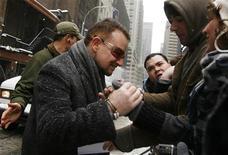 """<p>El músico Bono de la banda U2 saluda a admiradores en Nueva York, 2 mar 2009. El nuevo disco de la banda irlandesa U2, """"No Line On The Horizon"""", sería el álbum número uno en Gran Bretaña al fines de esta semana, tras vender 65.000 copias el día de su lanzamiento, indicaron el martes cifras de la industria y la Official Charts Company. REUTERS/Lucas Jackson</p>"""