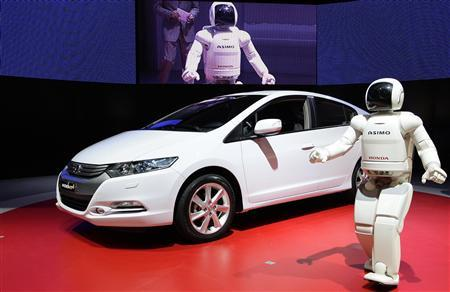 Honda's humanoid robot ''Asimo'' unveils the new Honda Insight hybrid car during the first media day of the 79th Geneva Car Show at the Palexpo in Geneva March 3, 2009. REUTERS/Valentin Flauraud