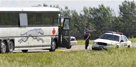 Police investigate the scene around a Greyhound bus about 20 km (12 miles) west of Portage la Prairie, July 31, 2008. REUTERS/Fred Greenslade