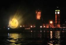 "<p>A logo to promote the film ""The Watchmen"" is projected onto fine spray water screen over the River Thames near to the Houses of Parliament in London March 4, 2009. REUTERS/Luke MacGregor</p>"