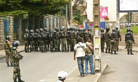 Members of the press are seen near riot police officers standing guard during a demonstration by opposition supporters in Madagascar's capital Antananarivo March 5, 2009. REUTERS/Rasoanaivo Clarel Faniry