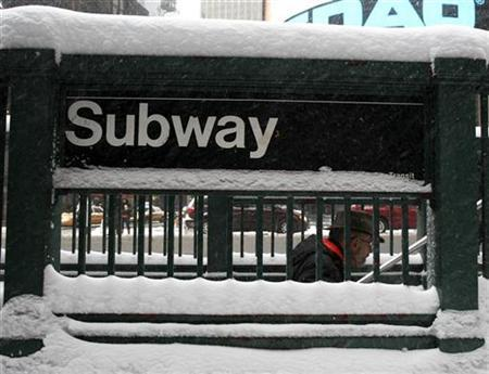 A morning commuter walks out of the subway in New York's Times Square March 2, 2009. REUTERS/Brendan McDermid
